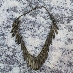 Gold colored feather charm necklace